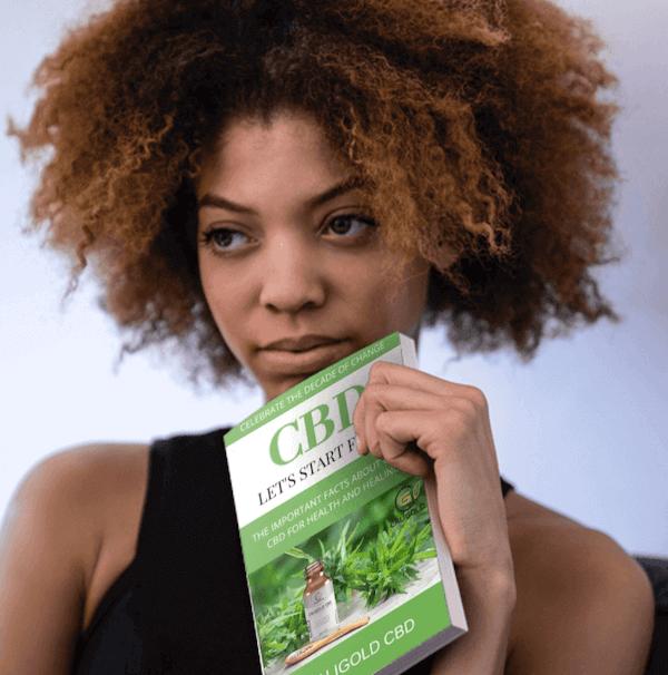 Women Holding CaliGold CBD Ebook